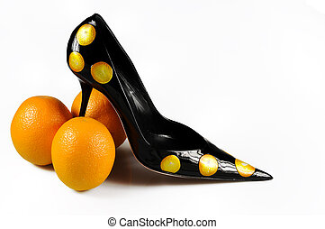 Women shoe with three oranges isolated on white