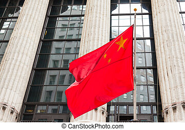 Chinese flag floating in front of a goverment building