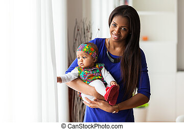 Young african american mother holding with her baby girl