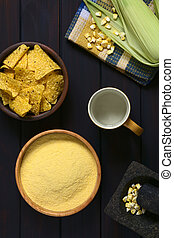 Cornmeal - Overhead shot of cornmeal in wooden bowl with cob...