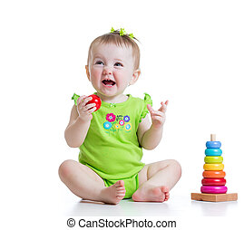 toddler girl playing with colorful toy pyramid