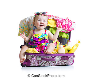 Baby girl sitting in trunk with things for vacation travel -...