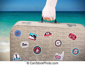 hand holds a suitcase with stickers on background of the sea