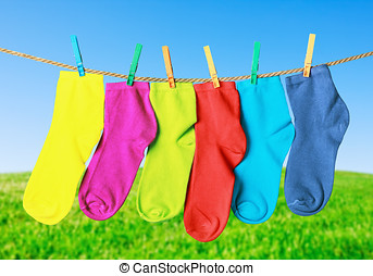 colorful socks hanging from a rope on the background of...