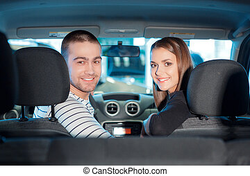 Couple inside the new vehicle in showroom - Ready for the...