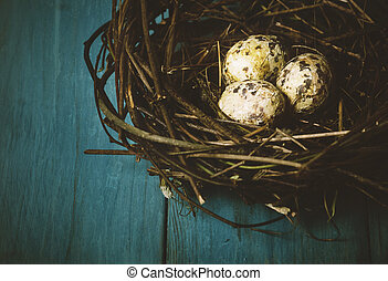 Eggs in Nest - Nest with eggs on wooden blue table. Texture...
