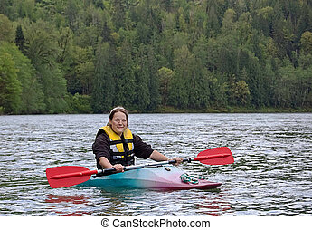 Young Woman Kayaking on River