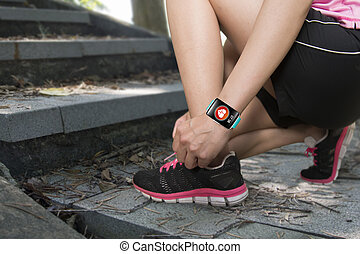 Sport woman tying shoelaces wearing health sensor smartwatch...