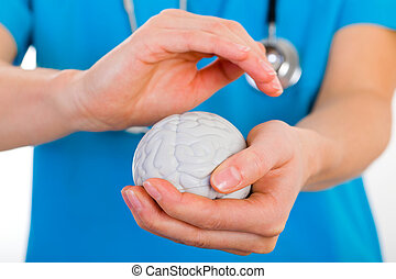 Mental health - Young doctor holding a plastic brain in...