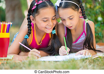 Sisters reading book in summer park - Hispanic sisters...