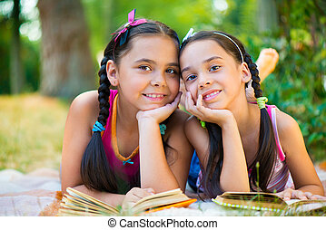 Portrait of two hispanic sisters reading in the park -...