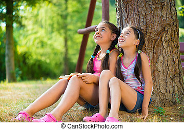 Hispanic sisters sitting under the tree and talking - Two...