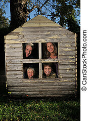 Family in the windows of a very small house with grass