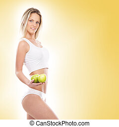 Young sexy woman in sporty clothes with an exotic fruit in her h