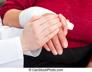Bandaged thumb - Young doctor giving helping hand for the...