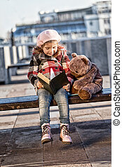 little girl in a pink beret sits on a bench in sunny autumn day and reads the book to a toy bear