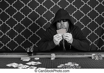 A man playing poker sitting at a table