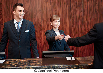 Reception at work in hotel - Here is your key. Receptionists...