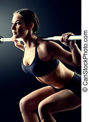 squats with rod - Strong young woman with beautiful athletic...