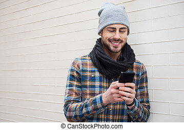 Typing message to friend Handsome young man holding mobile...