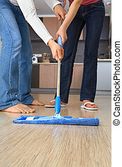 Cleaning - Two people are cleaning the house with one and...