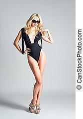 Studio fashion shot: a beautiful girl wearing swimsuit and sunglasses