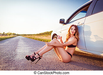 Sexy young woman sitting at car and drinking water - Sexy...