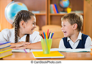 Cute schoolchildren having fun in classroom