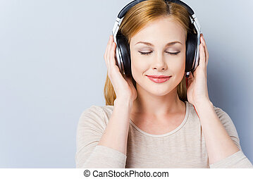 Music waves. Beautiful young women in headphones keeping eyes closed and smiling while standing against grey background