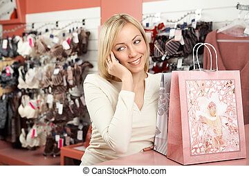 The woman shop and a mobile phone - The blonde calls on...