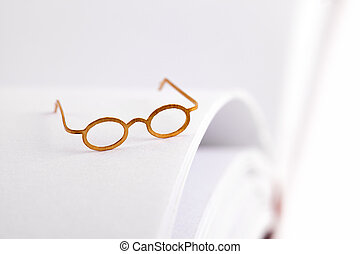 Reading glasses on a white page - Reading glasses on a open...