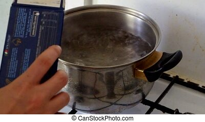 Putting spaghetti into the boiling water side view