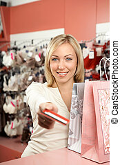 Pay off with a card for purchases - The woman stretches...