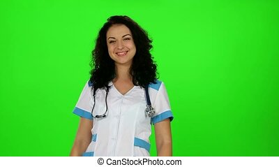 Smiling beautiful nurse standing in a white coat with...
