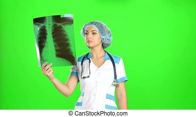 Young female doctor looking at the x-ray picture of lungs in...