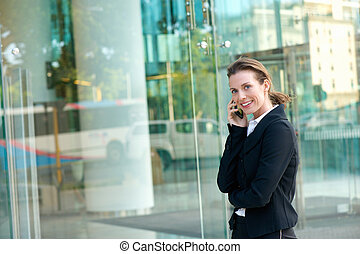 Happy business woman walking and calling by mobile phone -...