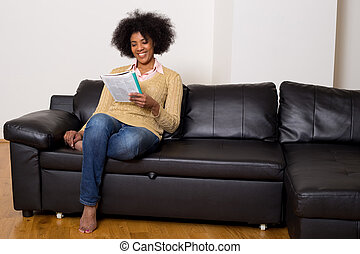 young woman reading a magazine at home
