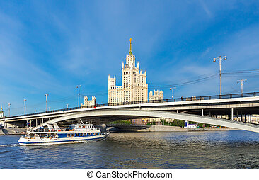 Cruise boat on Moscow river with Kotelnicheskaya skyscraper...