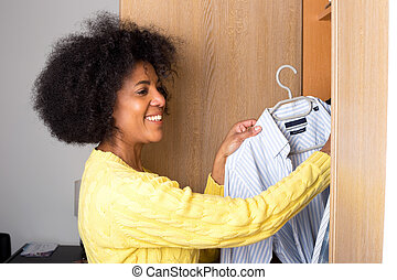 a young woman at home taking a shirt out of a wardrobe for...