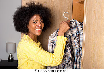 young woman taking a shirt out of a wardrobe