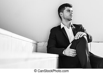 Young businessman near a office building wearing black suit...