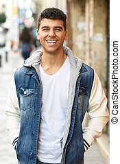 Handsome young man with blue eyes walking in the street -...