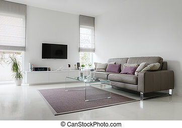 White living room with taupe leather sofa and glass table on...