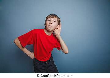 Boy, teenager, twelve years old, in a red shirt, holding...