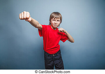 Boy, teenager, twelve years red in shirt, showing fists -...