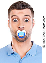 Like a baby. Funny young man with big eyes and pacifier in...
