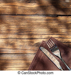 Empty board with fork and knife on wooden table. Top view