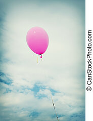 A pink balloon with string on a blue sky background