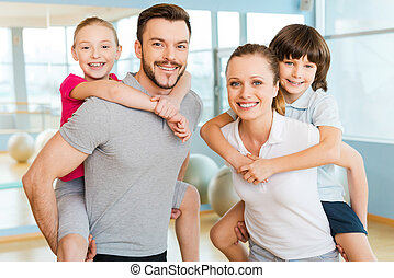 Sporty family. Happy sporty family bonding to each other while standing in sports club together