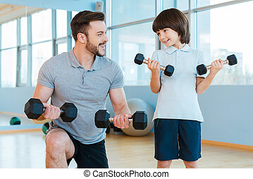 Exercising together Happy father and son exercising with...